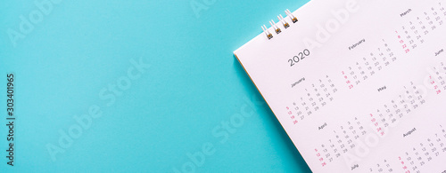 Obraz close up top view on white calendar 2020  month schedule to make appointment meeting or manage timetable each day lay on blue background for planning work and life concept - fototapety do salonu