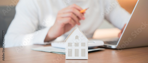 Fototapeta close up on house model with man working about  check and summary expense of home loan mortgage for refinance plan , people lifestyle concept obraz
