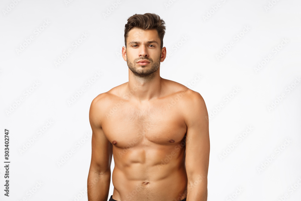 Fototapeta Waist-up shot confident good-looking, sexy young tanned man, athlete standing naked torso, squint, showing six-pack perfect body, train in gym, workout daily, lead active lifestyle. Bodybuilder promo
