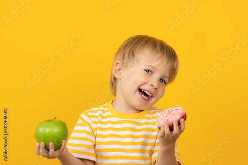 Happy child holding donut and apple