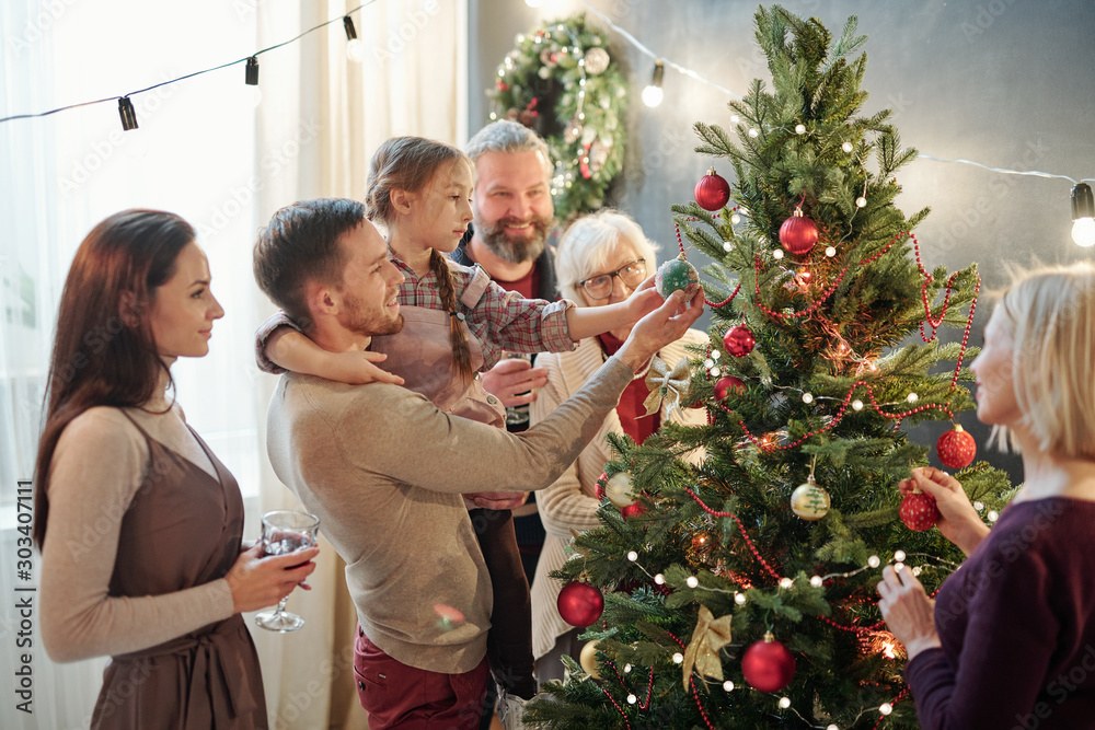 Fototapeta Young man with little daughter and other family members standing by xmas tree