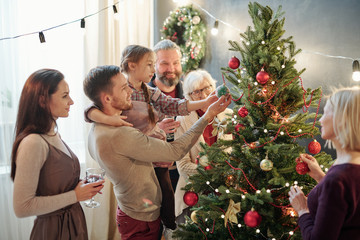 Young man with little daughter and other family members standing by xmas tree