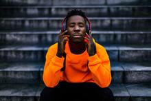 African-american Man In Stylish Orange Hoodie Sweatshirt In Wireless Headphones Listening Music And Enjoying Music On Background Of Stairs
