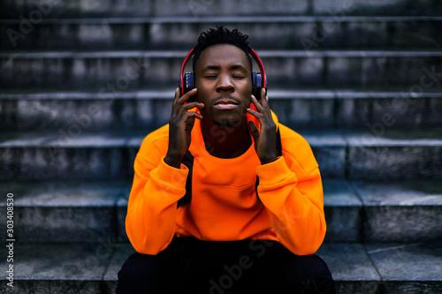 Valokuvatapetti african-american man in stylish orange hoodie sweatshirt in wireless headphones