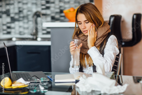 Valokuva  Sick blonde woman in scarf taking a prescribed pill with a glass of water at home kitchen