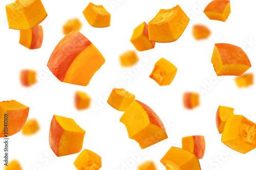 Fotomural  Falling piece of pumpkin, cubes, isolated on white background, selective focus