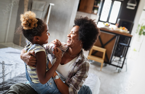 Fotomural  Happy mother playing, having fun, hugging with her daughter at home