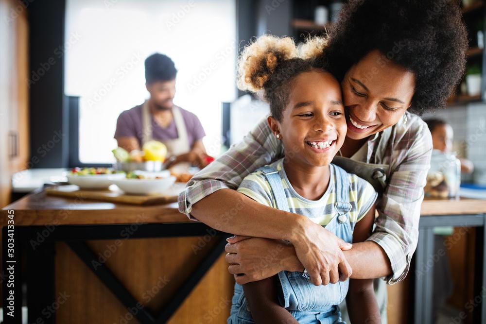 Fototapeta Mother and child having fun preparing healthy food in kitchen