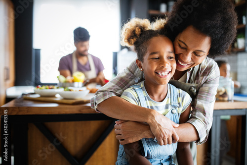 Mother and child having fun preparing healthy food in kitchen - 303413345