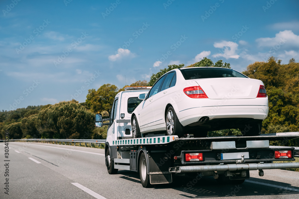 Fototapeta Car Service Transportation Concept. Tow Truck Transporting Car Or Help On Road Transports Wrecker Broken Car. Auto Towing, Tow Truck For Transportation Faults And Emergency Cars . Tow Truck Moving In