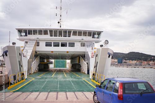 Ferryboat loading or unloading by a port pier Fototapeta