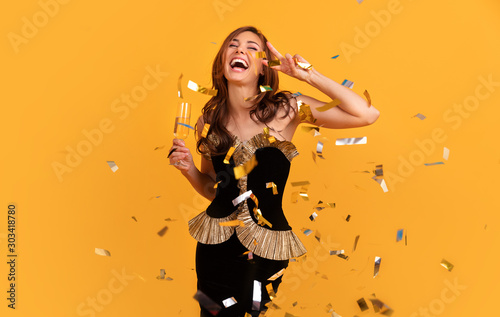 Young stylish woman on white background drinking champagne, celebrating new year, wearing black dress and yellow crown, happy carnival disco party, sparkling confetti, holding glass, having fun - 303418780