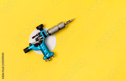 Canvas Print Blue tattoo machine on yellow background