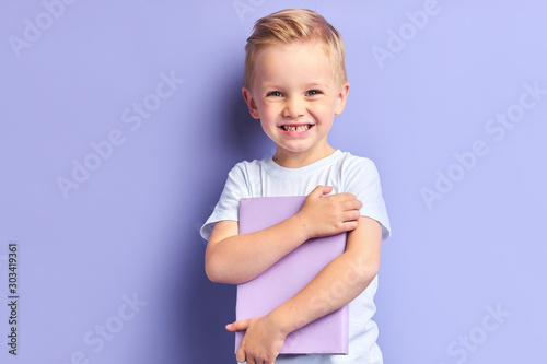 Portrait of blond kid boy holding book happily looking at camera , purple background Wallpaper Mural