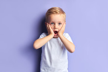 Beautiful Blue Eyed Boy Kid Surprised, Stand With Opened Mouth Looking At Camera. Isolated Purple Background