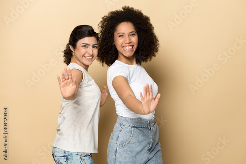 Fotografía Smiling beautiful diverse girls dancing, standing with arms outstretched