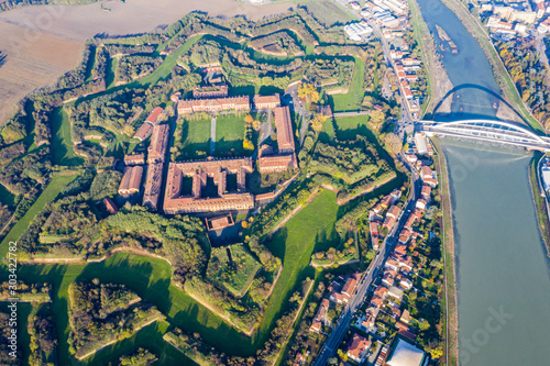 Fotografie, Obraz Aerial view of walls and bastions of modern six-star hexagon shaped fort Cittadella of Alessandria on winding river Tanaro