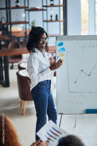 Confident african woman in eyeglasses, wearing white shirt and jeans, using diagrams, motivated african American speaker coach present business plan on whiteboard for workers in modern office - 303430323