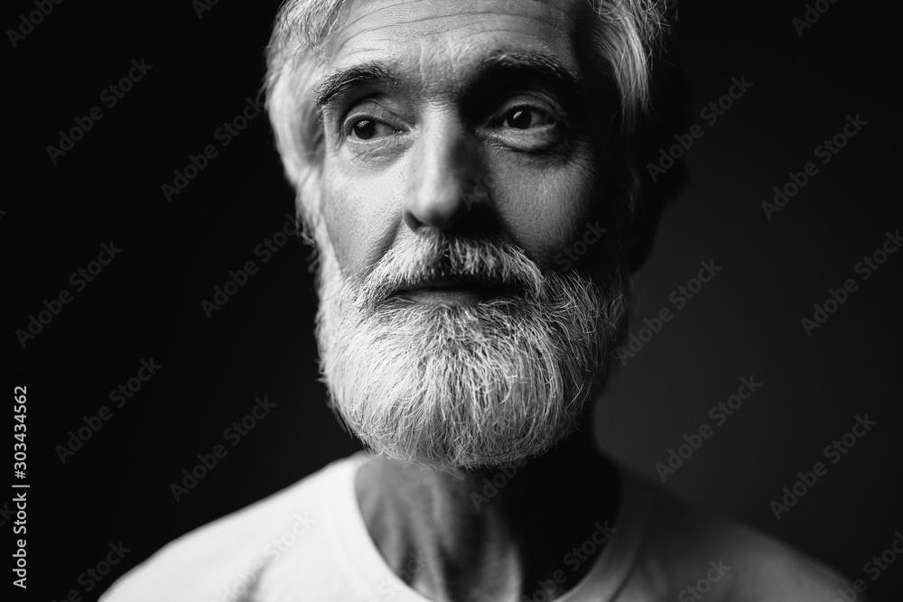 Fototapeta Close up studio portrait of handsome senior man with gray beard.