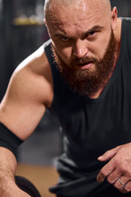 Powerful Strong Young Man With Thick Stylish Beard And Bald Head Looking At Camera With Evil Eyes, Ready To Start Training In Gym Hall, Professional Sport Concept