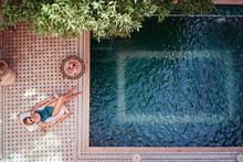 Enjoying Suntan. Vacation Concept. Top View Of Young Woman Near Private Swimming Pool In Beautiful Moroccan Backyard.