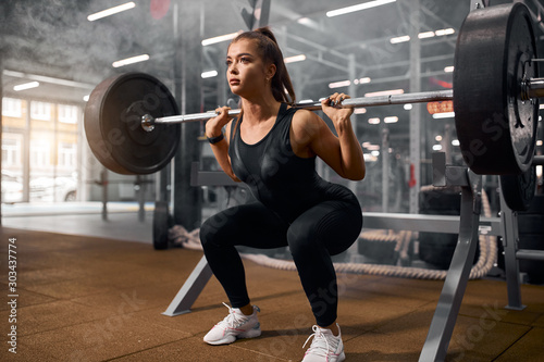 beautiful sporty weightlifter holding heavy metal professional barbell, prepa...