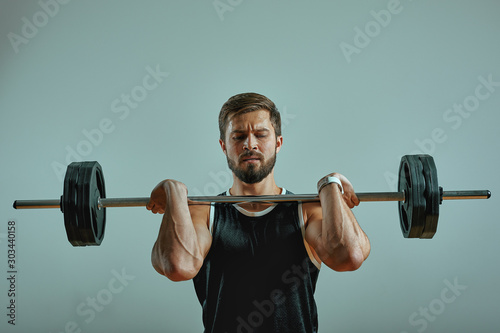 Portrait of super fit muscular young man working out in gym with barbell on gray background, copyspace Wallpaper Mural