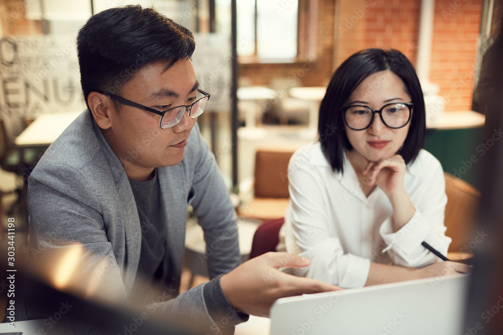 Portrait of two modern Asian business people discussing startup project while pointing at laptop in office