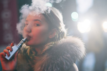 Beautiful Caucasian Girl In Winter Clothes On The Street, She Has Jacket's Fur,she Smokes An Electronic Cigarette, Vaping Out Smoke With A Self Confident Gesture, Illuminated By A Street's Ads Panel