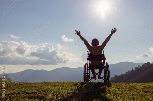 Obraz Happy disabled child in a wheelchair and stretching hands at sunset. back view, - fototapety do salonu