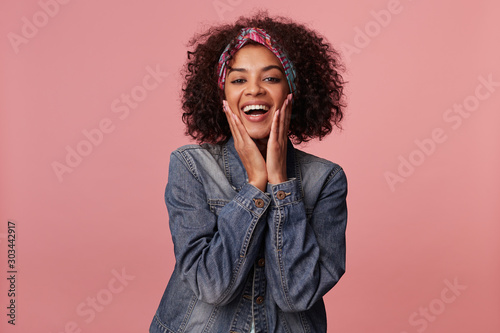 Valokuva  Joyful attractive young curly brunette woman with dark skin wearing casual hairs