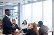 Personable black employee explains to foreign colleagues new client management strategy idea at modern group office training