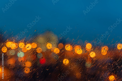 Obraz Abstract blurred picturesque background. Night defocused view of the city lights through the window with raindrops - fototapety do salonu