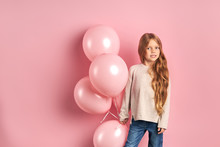 Cute Girl Of Caucasian Ethnicity Holding Pink Air Balloons Isolated Over Pink Background. She Has Long Hair And Big Beautiful Eyes