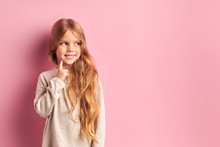 Portrait Of Thoughtful Little Caucasian Girl Cutely Dream About New Toy, Doll. Isolated Pink Background