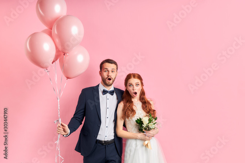 Photo wedding couple posing together isolated over pink background