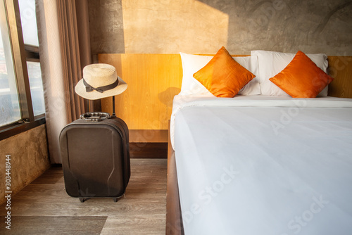 A suitcase with hat in comfortable hotel bedroom in cozy style Wallpaper Mural