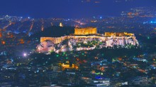 Cityscape Of Athens With Illuminated Acropolis Hill, Pathenon And Herodium Construction And Sea At Night. Athens Skyline At Night Viewed From Mount Lykavitos With Acropolis, Greece. Shot In Dusk.