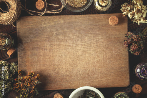 Cutting wooden board with various dried medicinal herbs and devices Canvas Print