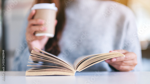 Closeup image of a woman holding and reading a book while drinking coffee on woo Canvas Print