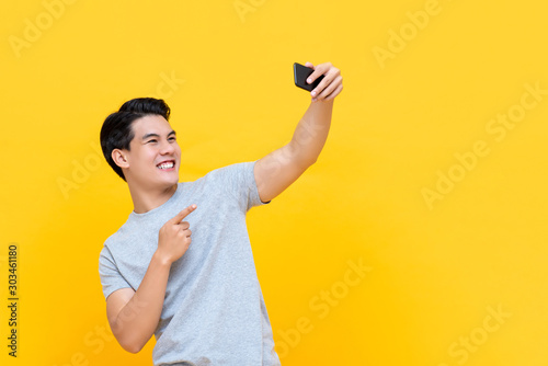 Fotografía Young smiling handsome Asian man taking selfie with smartphone