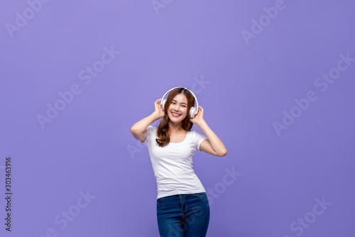 Obraz Pretty Asian woman dancing and listening to music on headphones - fototapety do salonu