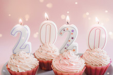 2020 Candles On Cupcakes With Whip Cream Frosting Using Pink Silicone Reusable Cups On Pink Fairy Lights Background, Happy New Year Sweet Food Concept