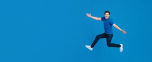 Energetic Young Man Jumping And Smiling With Outstretched Hands