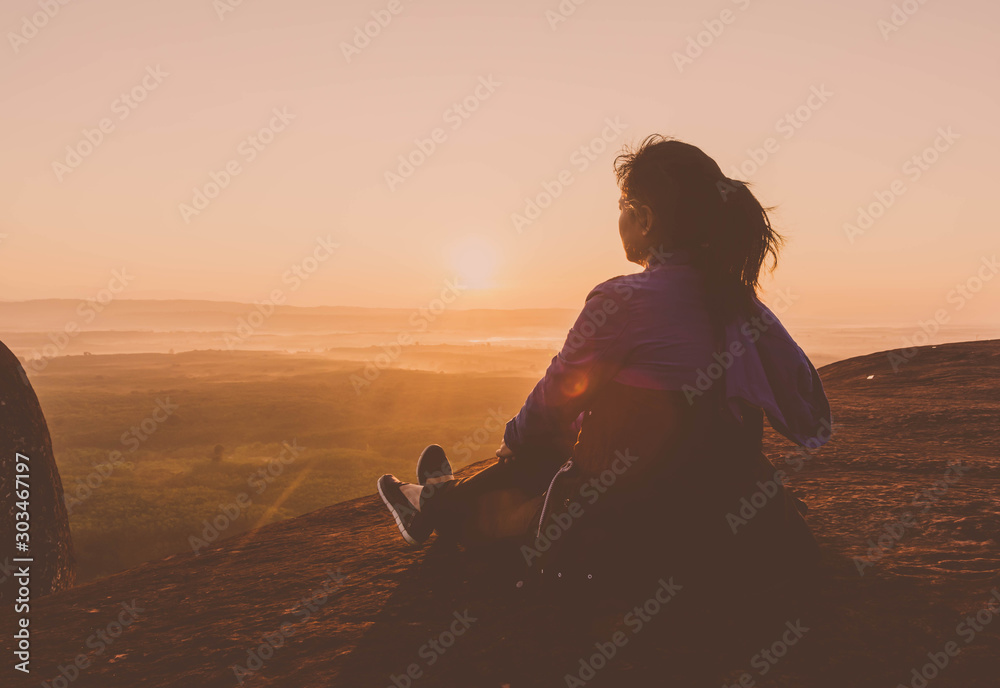Fototapety, obrazy: Young woman sitting on peak hill lookup mountain and forest at morning sunlight background. Happy gril relaxing concept.