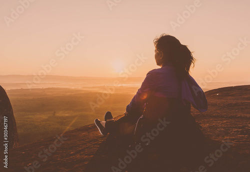 Fotomural  Young woman sitting on peak hill lookup mountain and forest at morning sunlight background
