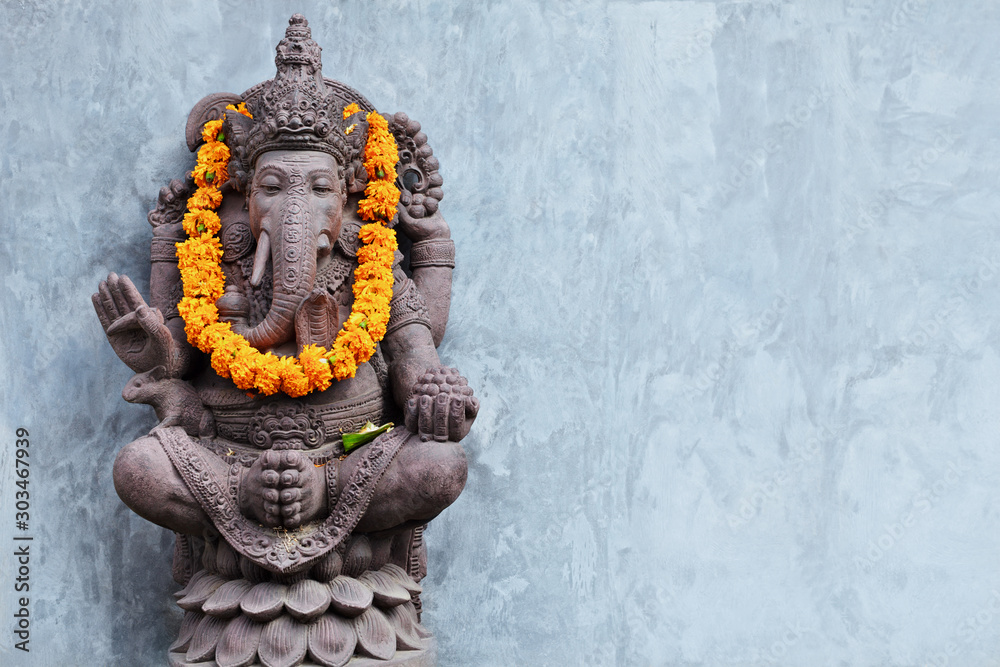 Fototapeta Ganesha sitting in meditating yoga pose in front of hindu temple. Decorated for religious festival by orange flowers garland, ceremonial offering. Balinese travel background. Bali island art, culture.