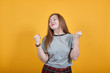 Young woman standing over isolated orange background very happy and excited keeping thumbs up with arms raised, smiling for success, closed eyes.