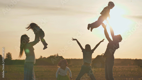 Obraz The concept of a happy large family. Happy parents tossing their children up on a sunset background. - fototapety do salonu