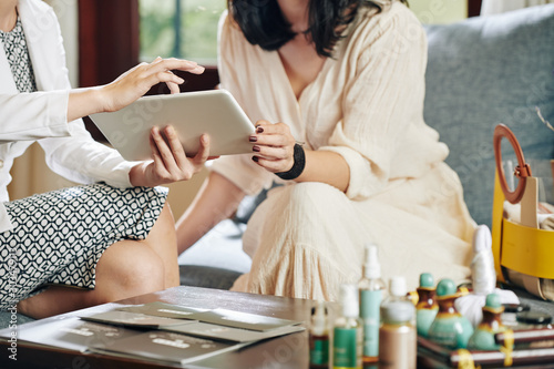 Obraz Beautician showing information about new cosmetics and beauty products on tablet computer to client - fototapety do salonu